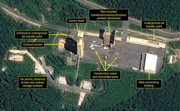 This July 22 satellite image, released and annotated by 38 North on Monday, shows what the U.S. research group says is the partial dismantling of the rail-mounted transfer structure (center) at the Sohae launch site in North Korea.