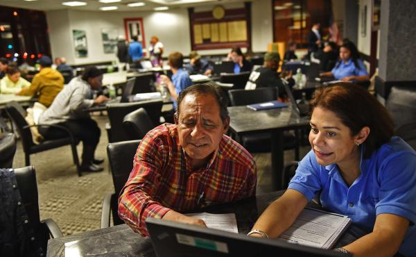 Elisa Carrero assists Julian Gauiria, of Paterson, N.J., with enrollment in the health insurance exchange in November. Signups continue to be brisk, health officials say.