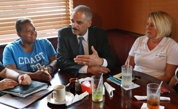 Attorney General Eric Holder talks with Ferguson, Mo., residents Angela Whitman (left) and Jill Richards on Wednesday at Drake's Place Restaurant about issues surrounding the shooting of Michael Brown.