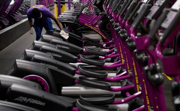 A Planet Fitness employee cleans equipment before a gym's reopening in March in Inglewood, Calif., after being closed due to COVID-19. Reduced access to recreation likely has contributed to weight gain during the pandemic.
