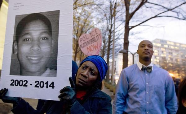 Tomiko Shine holds up a picture of Tamir Rice during a 2014 protest in Washington, D.C. Timothy Loehmann, the police officer who shot and killed the 12-year-old boy, was fired Tuesday for answers he provided on his personal history statement during the hi