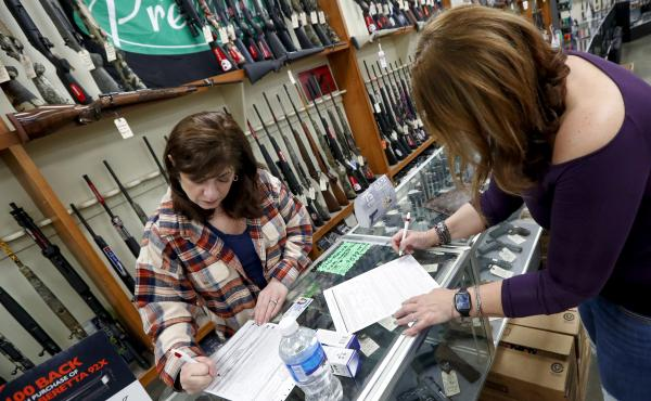 Andrea Schry (right) fills out the buyer's part of legal forms to buy a handgun as shop worker Missy Morosky fills out the vendor's parts after Dukes Sport Shop in New Castle, Pa., reopened on Wednesday.