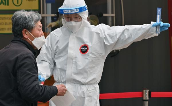 A medical staffer wearing protective gear gestures after collecting a swab from a visitor to test for the coronavirus at a temporary testing station in Seoul in December 2020.  South Korea on Friday announced it would raise restrictions in the capital reg