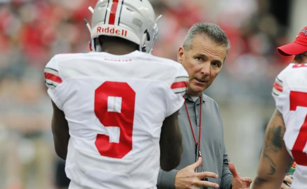 Ohio State head coach Urban Meyer, talks with a player in April in Columbus, Ohio. The coach, who has won three national titles, including one for the Buckeyes, has been suspended as Ohio State investigates whether he failed to report an assistant coach's