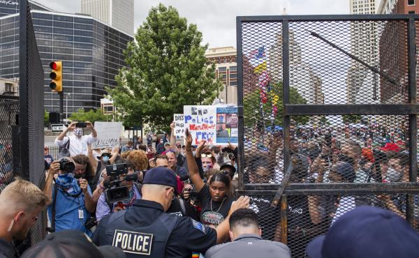 Protesters gather outside the entrance to a rally for then-President Donald Trump in June in Tulsa, Okla. A new state law increases penalties for protesters who block public roadways and grants legal immunity to drivers who unintentionally harm them as th