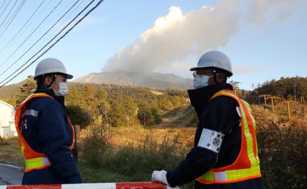 Security personnel guard the entrance of a road leading to a trail on Mount Ontake in Nagano prefecture Tuesday, three days after the volcano erupted in central Japan.