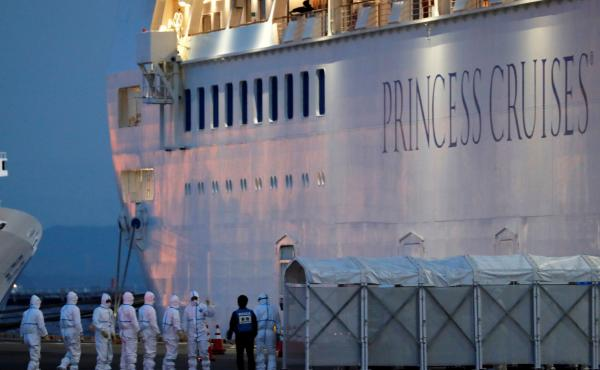 Officers wear protective gear as they work to remove people who tested positive for coronavirus from the cruise ship Diamond Princess. The ship is sitting at Daikoku Pier Cruise Terminal in Yokohama, south of Tokyo, on a 14-day quarantine.
