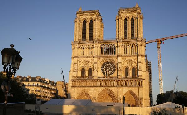 Notre Dame cathedral is seen at sunset Tuesday, after repair work stops due to the coronavirus outbreak. Wednesday marks the first anniversary of the devastating fire that destroyed many parts of the Gothic cathedral.