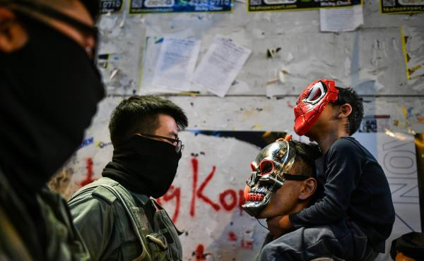 A police officer stares down a man and child wearing masks in the Lan Kwai Fong area of central Hong Kong.