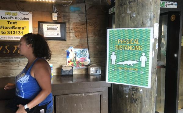 Signs posted at Flora-Bama show how far apart people should stand to maintain social distancing — an alligator's length.