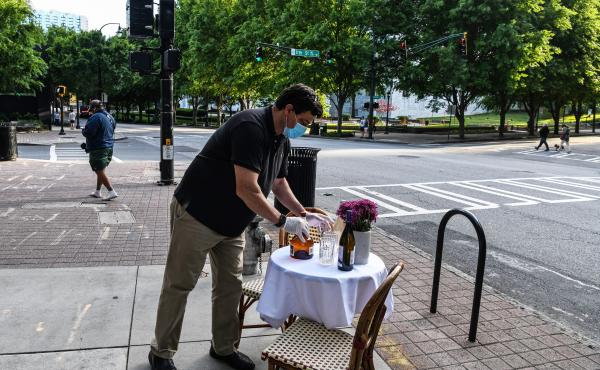 A man decorates a bistro table outside his restaurant amid the coronavirus pandemic in Atlanta on April 27. As states reopen, some are allowing restaurants to add outdoor seating in streets and parking lots.