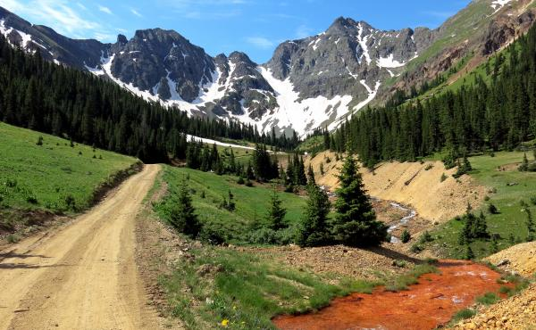 Orange sediment laced with heavy metals is visible in the path of water coming out of the Natalie/Occidental Mine in southwestern Colorado. This mine is one of dozens on a proposed Superfund listing pending with the EPA. Several mines in the area have bee