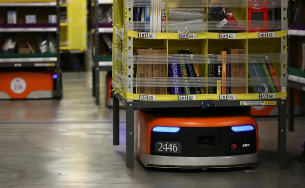 Robots move racks of merchandise at an Amazon fulfillment center in Tracy, Calif. When a robot finds its storage unit, it glides underneath, lifts it up and then delivers it to a worker.