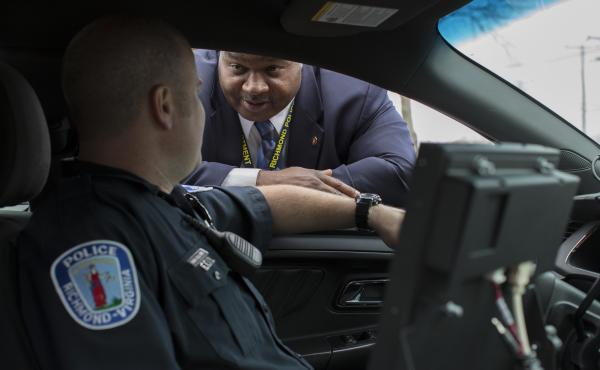"Detective Mark Williams (right) speaks with an officer in Richmond, Va. A decade ago, amid a surge in violent crime, Richmond police were identifying relatively few murder suspects. So the police department refocused its efforts to bring up its ""clearance"