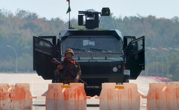 A soldier stands guard on a blockaded road to Myanmar's parliament in Naypyidaw on Monday, after the military detained the country's de facto leader Aung San Suu Kyi and other officials and activists.