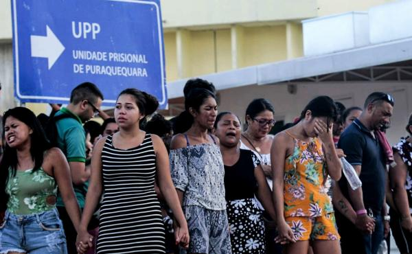 Family members of inmates wait and pray in front of the Puraquequara prison in the city of Manaus, the capital of northern Brazil's Amazonas state, on Monday. Dozens of inmates were killed in four jails in northern Brazil on Sunday and Monday, authorities