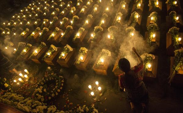 A woman spreads incense over the remains of 172 unidentified people who were discovered buried at what was once a Guatemalan military camp during the civil war in San Juan Comalapa, Guatemala, a day before their formal burial at the same site where they w