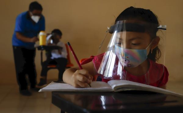 Wearing a mask and a face shield to curb the spread of the coronavirus, 10-year-old Jade Chan Puc writes in her workbook during the first day of class in Hecelchakán, Campeche state, Mexico, on April 19. On average, schools in Latin America and the Carib