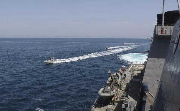 "In this Wednesday photo made available by U.S. Navy, Iranian Revolutionary Guard vessels sail close to U.S. military ships in the Persian Gulf near Kuwait. Eleven Iranian naval vessels made ""dangerous and harassing"" maneuvers near U.S. ships in the Gulf o"