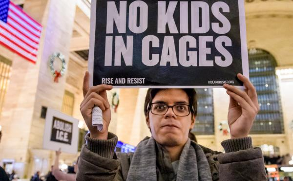 A demonstrator holds a sign at a silent protest about U.S. immigration policy at Grand Central Station in New York City.