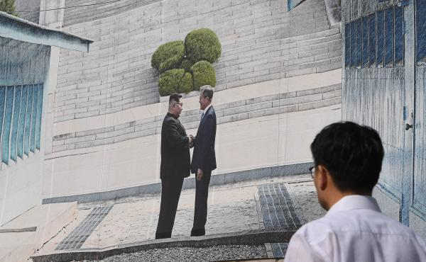 A man walks past a giant banner showing a picture of the summit handshake between South Korean President Moon Jae-in and North Korean leader Kim Jong Un, at Seoul City Hall on Sept, 13. Moon will fly to North Korea's capital on Sept. 18 for a third summit
