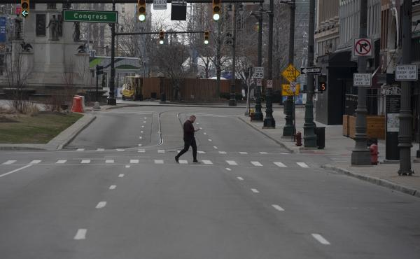 A man crosses an empty street in Detroit, Michigan on March, 24, 2020. - At 12:01 am Tuesday March 24,2020 Governor Gretchen Whitmer ordered a 'Stay at Home and Stay Safe Order' to slow the spread of Coronavirus (COVID-19) across the State of Michigan whi
