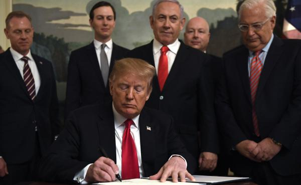 President Trump signs a proclamation at the White House on Monday officially recognizing Israel's sovereignty over the Golan Heights, with Israeli Prime Minister (center-right) among the officials looking on.