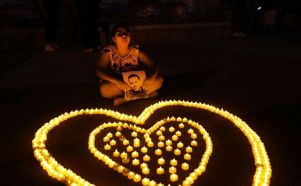 Nine-year-old Gabriella Santamaria holds up a picture of her uncle Stephen who died from a heroin overdose during a 2017 candlelight vigil for victims of drug addiction in Staten Island.