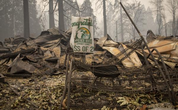 A sign for a recent graduate is bent but not burned in Blue River, Ore., eight days after the Holiday Farm Fire swept through its business district.