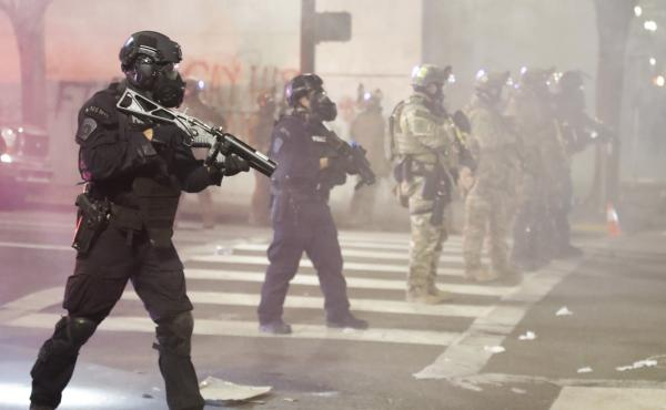 Federal officers deploy tear gas and crowd control munitions at demonstrators during a Black Lives Matter protest Tuesday at the Mark O. Hatfield U.S. Courthouse in Portland, Ore.