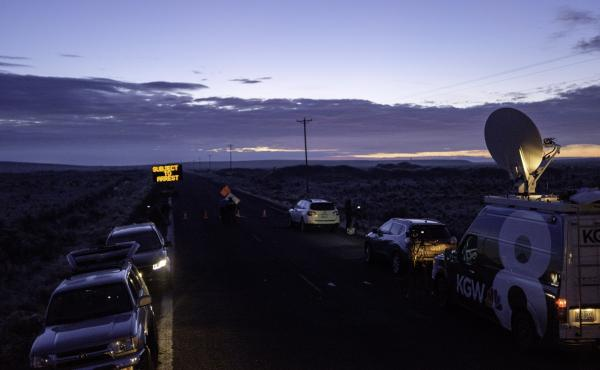 Media wait at a checkpoint about 4 miles from the Malheur Wildlife Refuge Headquarters near Burns, Ore., as the sun rises on Thursday. The FBI had surrounded the last four protesters holed up at a federal wildlife refuge in Oregon and were waiting for the