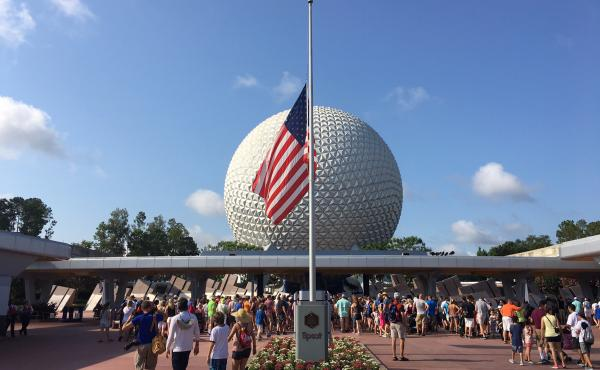 Tourists walk past the flag flying at half-staff at Disney's Epcot theme park in Orlando on Monday.
