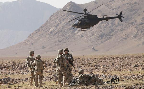 A Kiowa Warrior helicopter flies above soldiers with 4th Squadron 2d Cavalry Regiment during a live-fire exercise in the desert on March 6, 2014 near Kandahar, Afghanistan.