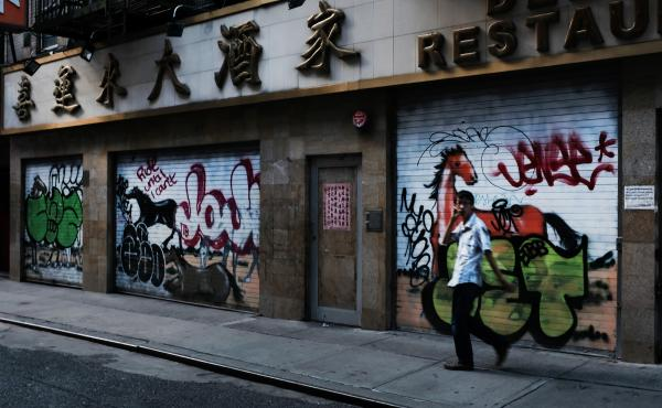A man passes by a closed restaurant in New York City's Chinatown on Aug. 10, 2020. The unemployment rate for Asian Americans has surged amid the pandemic, a trend that has been overlooked amid the widespread economic misery.