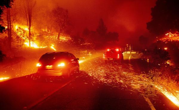 Vehicles pass through a roadway as the Kincade Fire burns through Sonoma County, Calif., on Thursday.