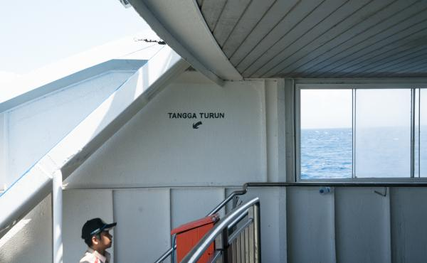 A ferry crew member walks from the truck level to where the passengers sit.