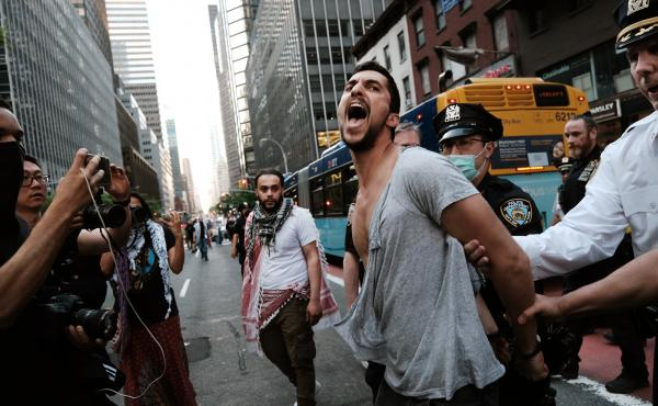 Police arrest a man after a group of pro Israelis got into a fight with protesters and activists condemning Israel and supporting Palestinians on May 18, 2021 in New York City.