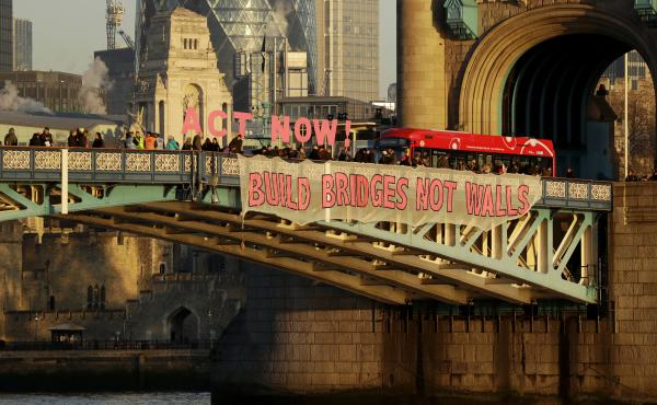 """""""Build Bridges Not Walls,"""" reads a banner held by demonstrators on London's Tower Bridge to protest Donald Trump's inauguration as U.S. president on Friday."""