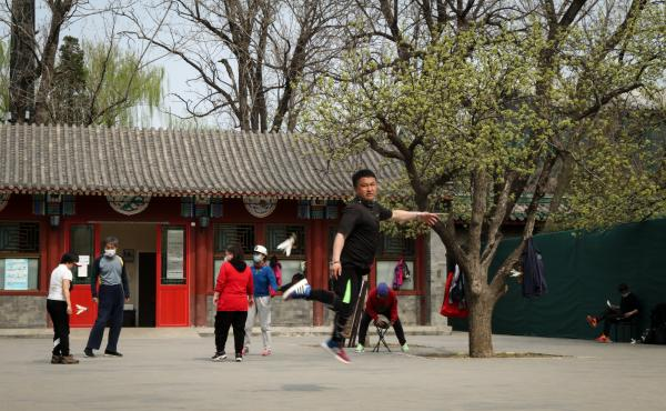 A skilled player of jianzi, or the Chinese equivalent of Hackey Sack, jumps to pass the feathered toy to the next participant.