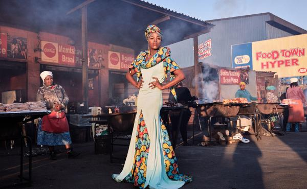 "Belinda Qaqamba Ka-Fassie poses at a community space where women cook and sell meat. She started drag as an escape from oppression she felt at Stellenbosch University for being ""black, Xhosa, poor, queer and effeminate."" ""It is through pageantry and perfo"