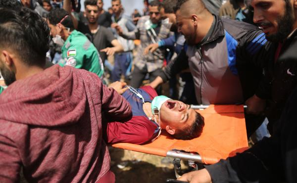 Palestinians carry a protester injured during clashes with Israeli security forces on the Gaza-Israel border on Friday.