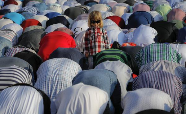 A child stands among the people taking part in Eid al-Fitr prayers in Bucharest, Romania. Members of the country's Muslim community gathered at the massive Dinamo soccer stadium in the Romanian capital.