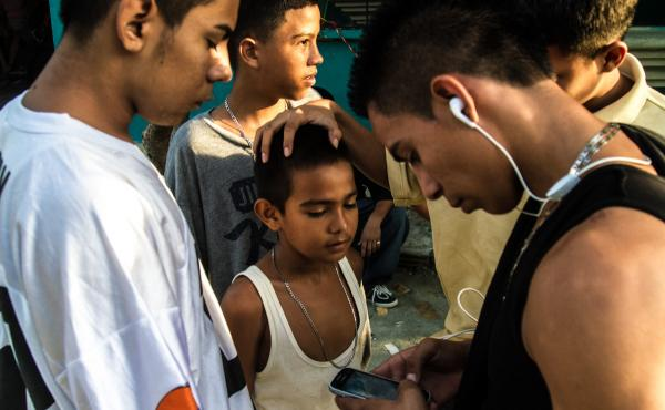 A group of older boys, some of whom are gang members, joke around with a younger boy. Neighborhood children are often groomed for gang activity from the age of 6 or 7. At first they may be given small assignments — like buying snacks for gang members or