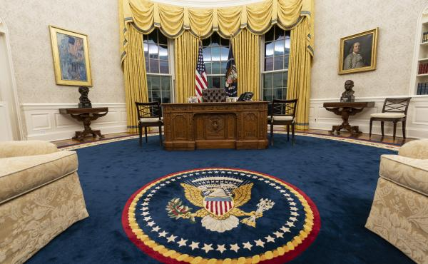President Biden kept the drapes and most of the furniture, but the rug and artwork in the Oval Office have changed. Flanking the Resolute desk are busts of  Abraham Lincoln, left, and Harry Truman. Above Lincoln is The Avenue in the Rain by Childe Hassam.