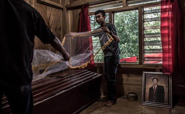 Suande, whose uncle died the previous month, lays a cloth over his uncle's coffin on the eve of the funeral.