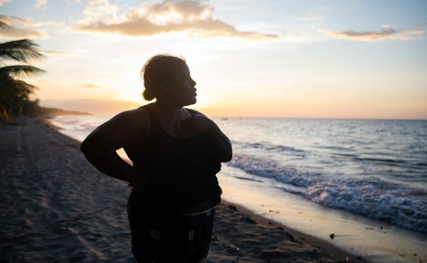 With the sun setting off the coast of northern Honduras, Ella Guity watches her daughters, Jirian and Eleny, swim in the warm Caribbean waters of the village of Rio Esteban, home to a group with African and indigenous roots known as the Garifuna. Ella had