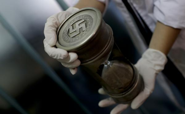 A member of the federal police holds an hourglass with Nazi markings on Friday at the Interpol headquarters in Buenos Aires, Argentina.