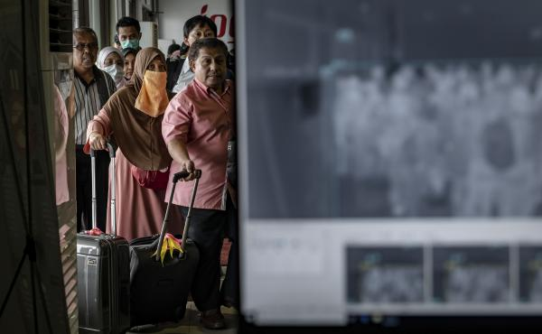 Passengers from an international flight have their temperature checked as they pass a thermal scanner monitor, seen at right, upon arrival at the international Airport in Yogyakarta, Indonesia on Thursday.