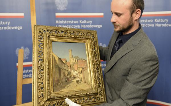 A museum worker carries a 19th century painting by Polish artist Robert Sliwinski during a ceremony Wednesday in Warsaw, Poland. The work was looted by the Nazis during World War II and recently recovered in the U.S. by the FBI.