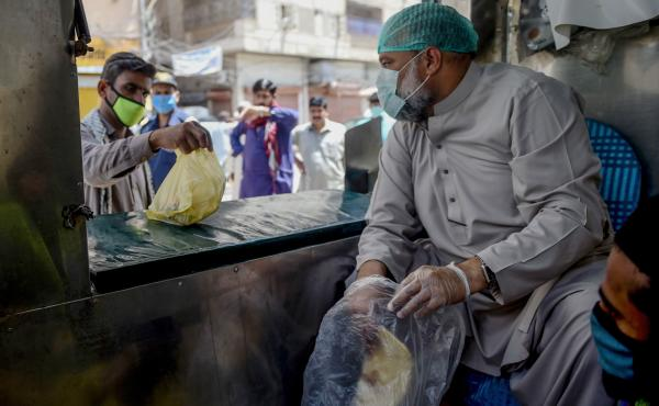 A municipal worker in Karachi hands out bags of food — part of government efforts to help those who've lost their livelihood during Pakistan's lockdown to stem the spread of the coronavirus.